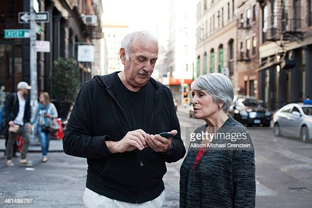 senior couple looking at smartphone in city