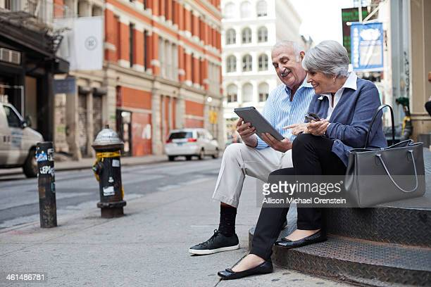 senior couple looking at ipad on stoop in city