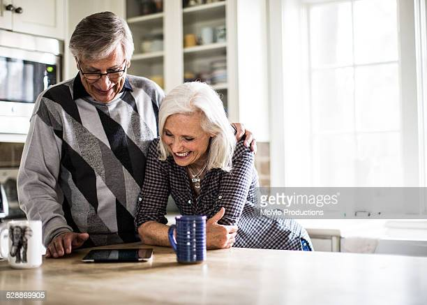 Senior couple looking at tablet in kitchen