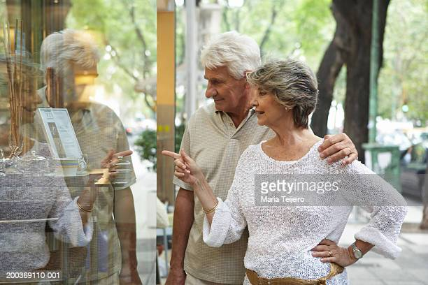 Senior couple looking in shop window, woman pointing