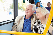 Senior Couple Enjoying Journey On Bus Looking Out Of The Window
