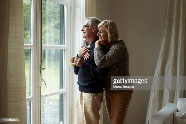 Senior couple looking out through door at home
