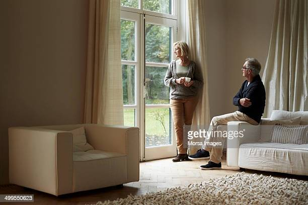 Senior couple looking out through house door