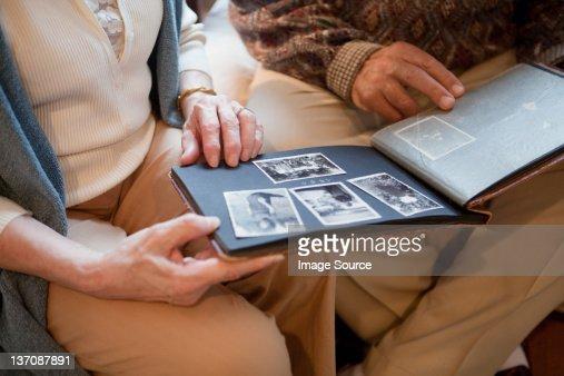 Senior couple looking through photo album, mid section : Stock Photo