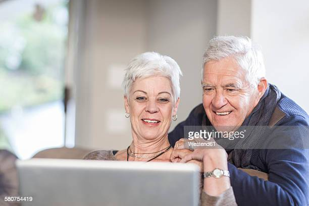 Senior couple looking together at laptop