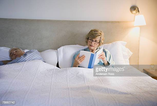 Senior couple lying on bed, woman reading book