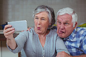 Senior couple making faces while taking selfie in kitchen