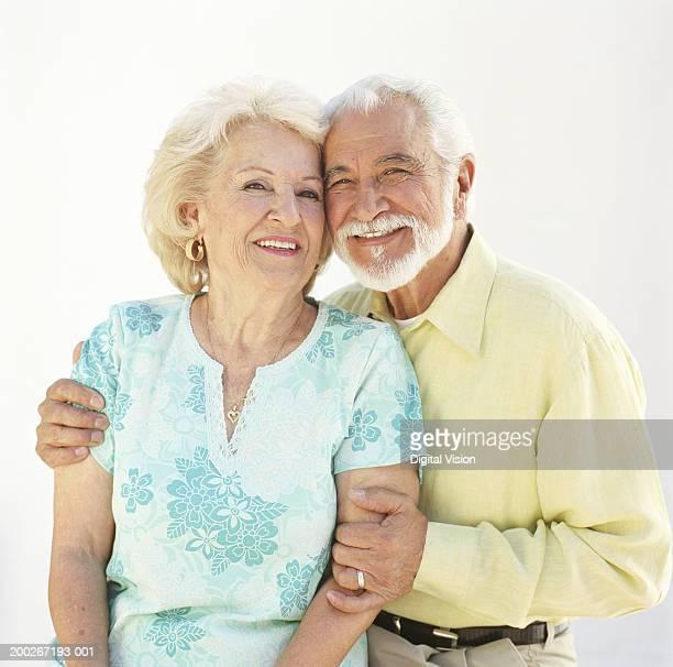 Senior couple, man embracing woman, smiling, portrait