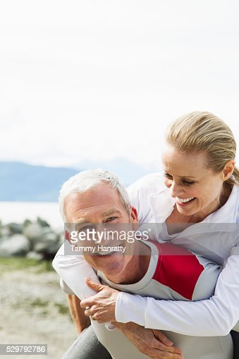 Senior couple, Man giving woman piggy back ride : Foto stock
