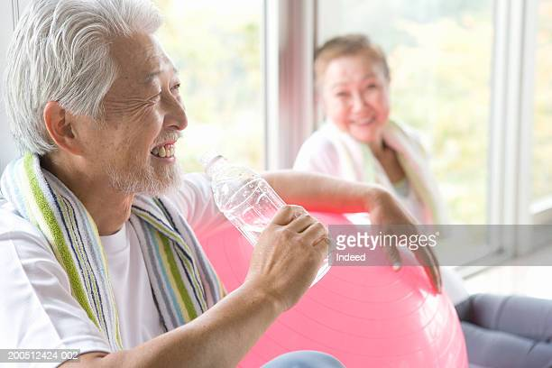 Senior couple, man holding bottle, resting arm on exercise ball