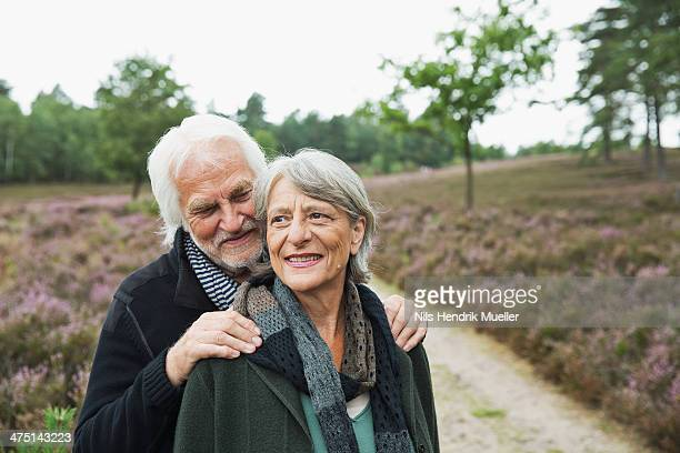 Senior couple, man with hands on woman's shoulders