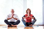 Active senior couple meditating at home, eyes closed.