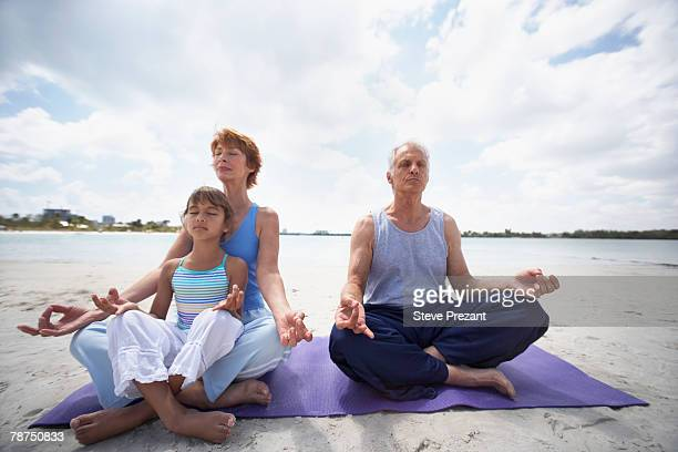 Senior Couple Meditating with Young Girl