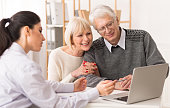 Senior couple meeting financial adviser for investment, looking at laptop in office