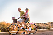two senior man and woman together on  an old bicycle outdoor activity. Happiness and freedom from work concept. sunlight and smiles.