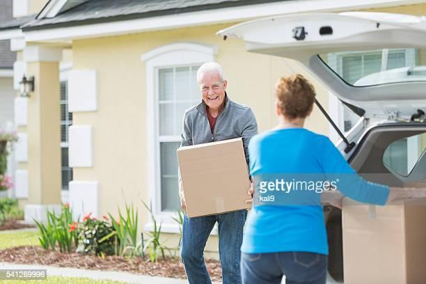 Pareja de edad mayor moviendo cajas en conexión de automóviles