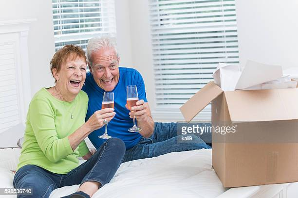 Senior couple moving house, celebrating with champagne