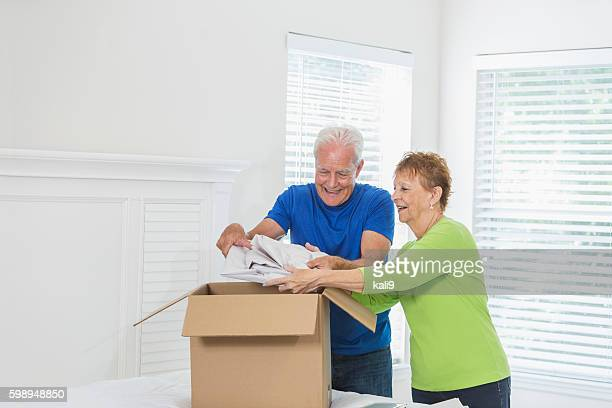 Senior couple moving house, packing box