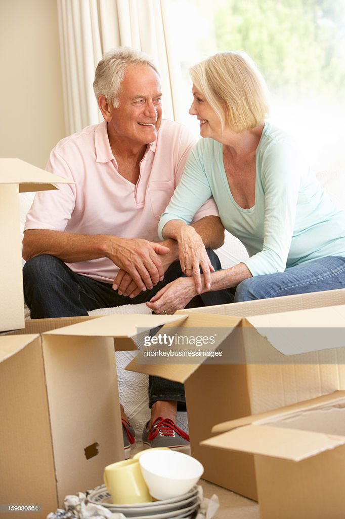 Senior Couple Moving Into New Home Surrounded By Packing Boxes : Stock Photo