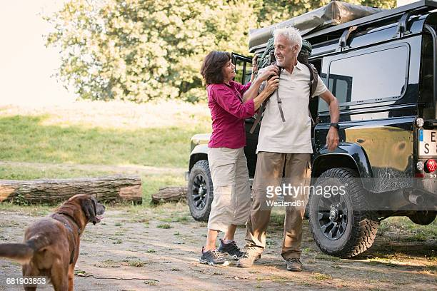 Senior couple next to cross country vehicle preparing for a hike