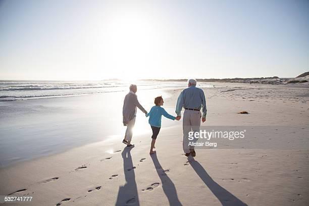Senior couple on a beach with their grandson