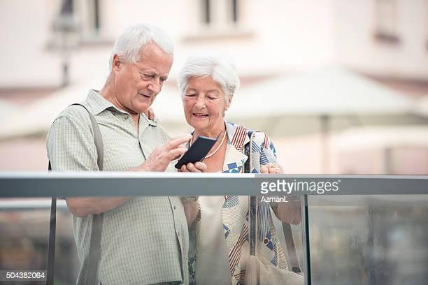 Senior couple on a city bridge using mobile phone