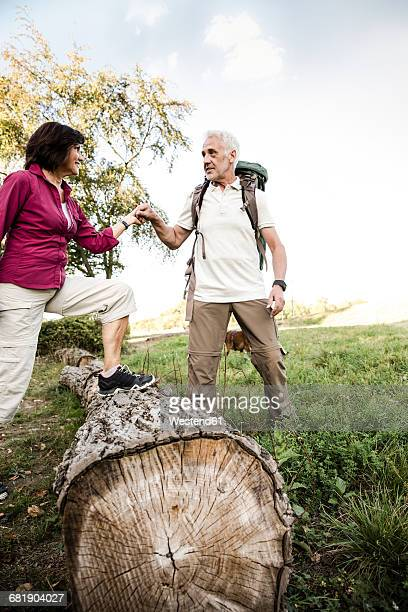 Senior couple on a hike crossing tree trunk