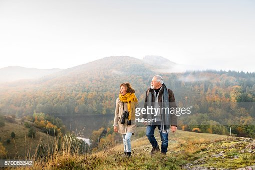 Senior couple on a walk in an autumn nature. : Foto stock