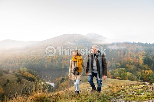 Senior couple on a walk in an autumn nature. : Stock Photo