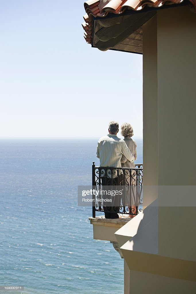 Senior couple on balcony overlooking ocean stock photo for Balcony overlooking ocean