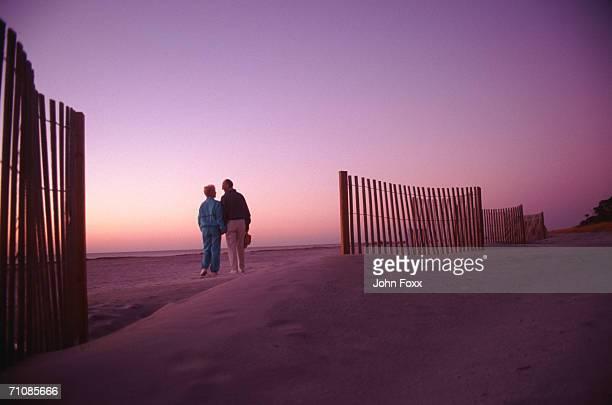 Senior couple on beach at sunset