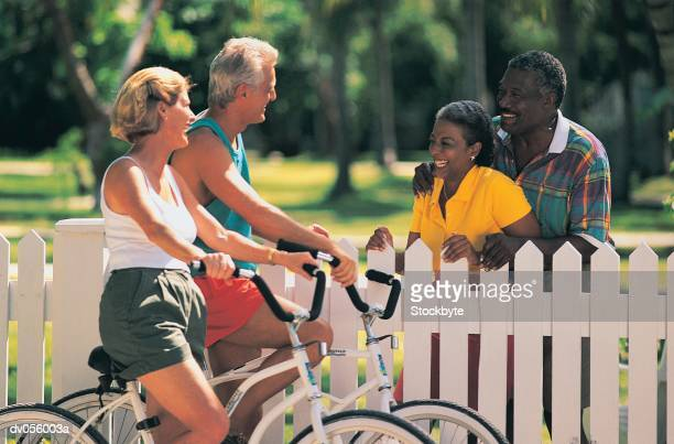 Senior couple on bikes, with African American senior couple