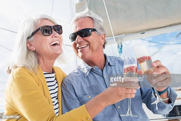 Altes Paar feiert mit Champagner auf dem Boot