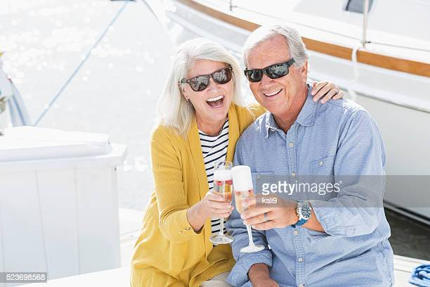 Senior couple on boat celebrating with champagne