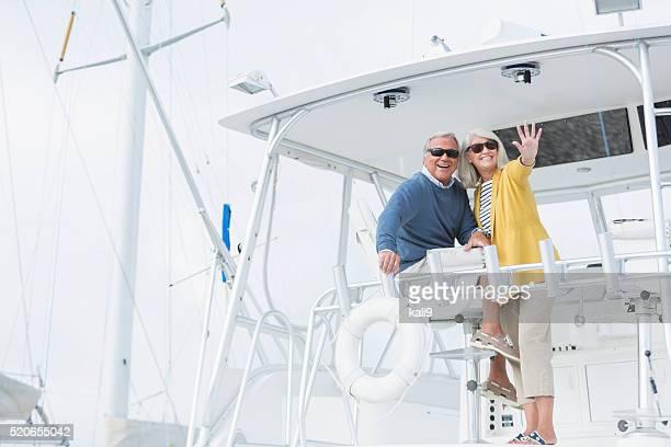 年配のカップルボートに着ているサングラス、手を振る