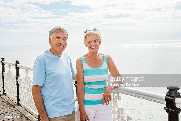 Senior couple on pier overlooking the sea.