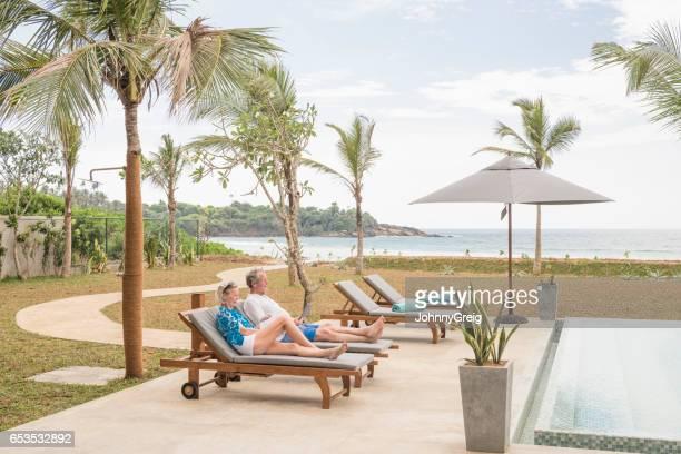 Senior couple on soun loungers at poolside