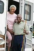 Senior couple on steps of a caravan