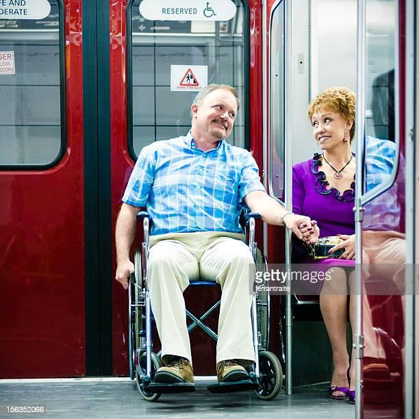 Couple Senior au métro accessible en fauteuil roulant