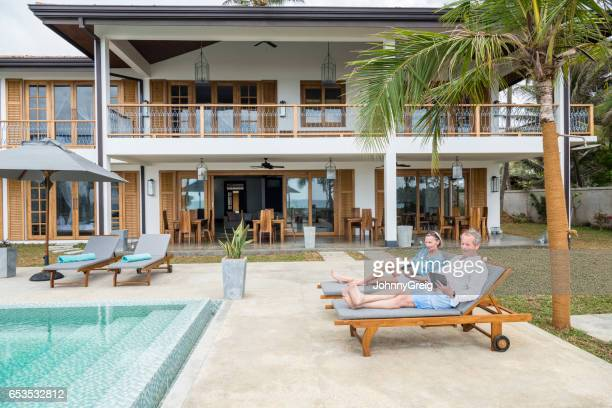 Senior couple on sun loungers at luxury holiday apartment