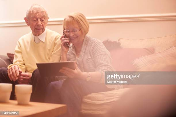 Senior couple on the phone and using digital tablet