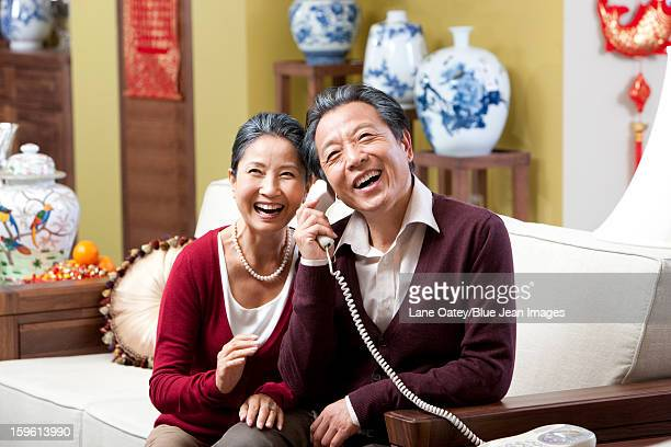 Senior couple on the phone during Chinese New Year