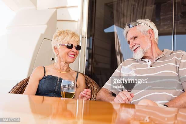 senior couple on yacht, enjoying wine on deck