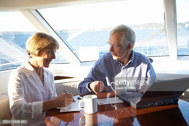 Senior couple on yacht, man using laptop and woman writing postcards