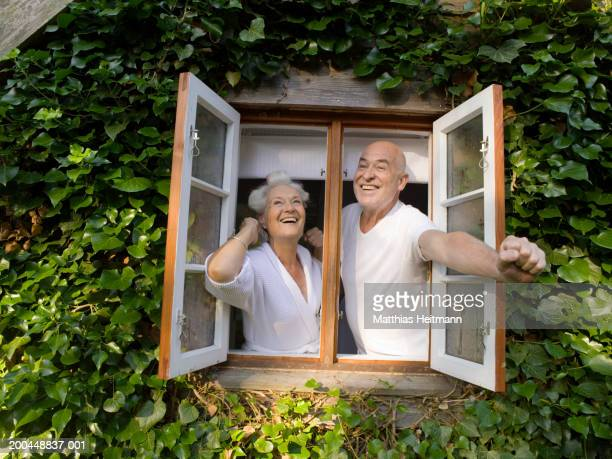 Senior couple opening window in morning, smiling