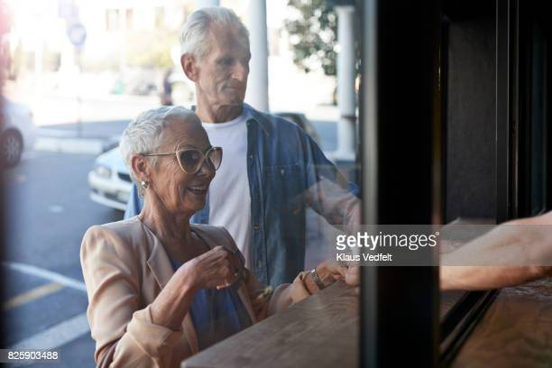 Senior couple ordering coffee to-go, at street bakery