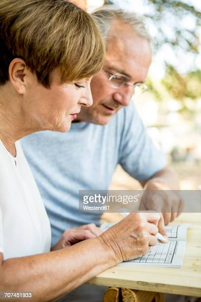 Senior couple outdoors doing crossword puzzle together