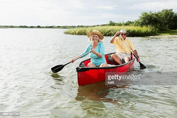 Senior couple paddling canoe with oars