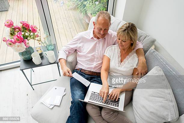 Senior couple paying bills online at home