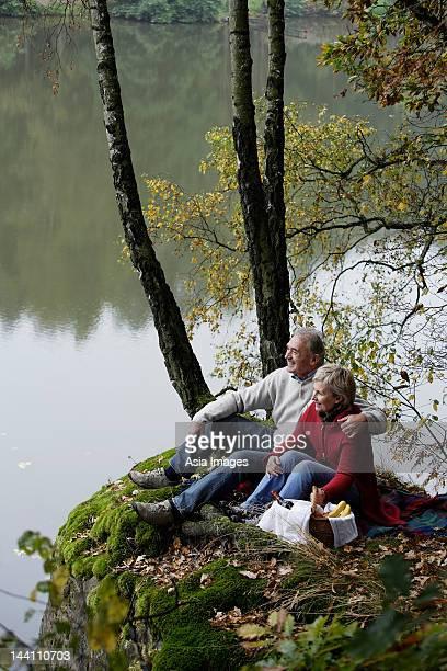 Altes Paar mit einem Picknick am See